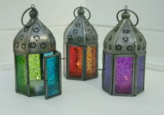 Mini fair trade Moroccan-style iron lantern with beautiful painted two-tone, patterned glass panels. Two panels are hinged like a door to allow the insertion of a tealight into the lantern (not supplied). Can be used inside or outside.