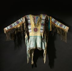 OGLALA SIOUX BEADED AND FRINGED HIDE WAR SHIRT of classic design.