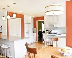 I would usually never think of painting a kitchen bright orange...but with all the white it totally works!