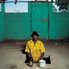 Servitor Homel Dorival, standing in a sacred space, poses with a ceremonial cup used in rituals, Soukri, Haiti, 1995 | Phyllis Galembo