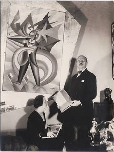 F. T. Marinetti and his wife, Benedetta Cappa Marinetti, in their Rome apartment in front of a portrait of Marinetti by Fortunato Depero, 1932.