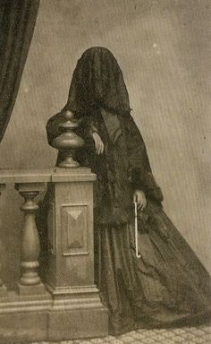 Full mourning attire, photographed circa 1860. I'm surprised she isn't wearing black gloves.