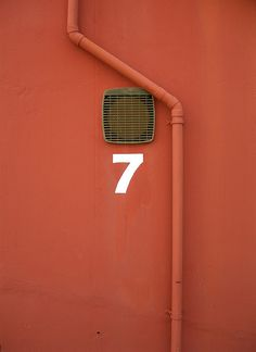 0 nuémro 7 blanc sur mur rouge - white number 7 on a red wall Number 7, Magic Number, Lucky Number, Wayfinding Signage, Letters And Numbers, Orange, Typography Design, Color Inspiration, Hand Lettering