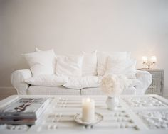 A fluffy white sofa, piled high with pillows.