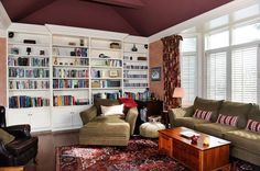 Living room with built-in bookshelves, vaulted ceiling and large windows.