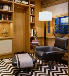 The large scale black and white Zigzag or Chevron patterned wool rug introduces movement and energy to the library of the New York East Side residence. The wire globe and the rounded forms of the floor lamp balance the angular patterns in the rug while the tan wood paneling adds warmth. Image courtesy Juan Montoya Design.