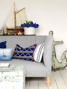 nautical decor, ticking sofa, striped pillows, boat model, trunk for coffee table, anchor.