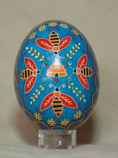 Hived bees and honeycomb goose pysanka on blue, pollinators pysanky