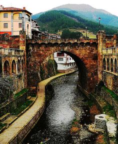 Potes, Spain.I remember dangling our feet in the river after a long steep walk and watching an elderly lady being led across the river in a very precarious fashion!.
