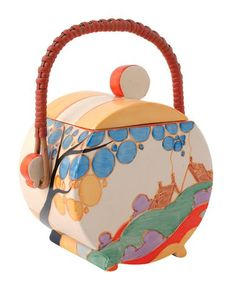 Clarice Cliff - BISCUIT BARREL This Clarice Cliff Fantasque Bizarre Bon Jour biscuit barrel has a cover and wicker handle in the 'Orange Secrets' pattern, a printed mark, and a tiny nick to the rim of the barrel.