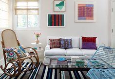 Com paredes e móveis claros, a sala seria um ambiente clean, não fossem as estampas diferentes que podem ser vistas nas almofadas e no tapete. Os desenhos nos quadros ajudam a dar um toque de cor