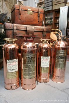 Collection of Antique Brass Fire Extinguishers displayed with a collection of Leather Cases   Beautiful red/copper colours   Restored Props   Clubhouse Interiors