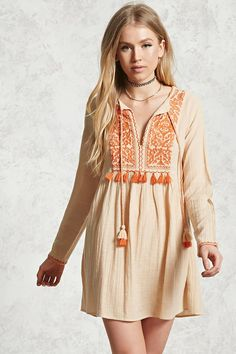 A textured woven peasant dress featuring an embroidered yoke with fringe trim, split neckline with braided tassels, long sleeves, embroidered sleeves, and a billowy silhouette.