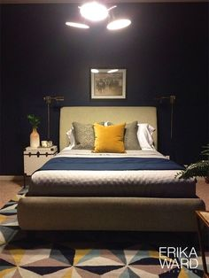 Designer Erika Ward - Masculine bedroom has a collected look with brass accents, deep navy blue walls, and a geometric Surya Frontier rug with bright blues and yellows. (FT-549) @mrserikaward