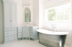 Blue bathroom features a cast iron tub and a vintage style tub filler placed under windows dressed in a white and grey geometric roman shade.