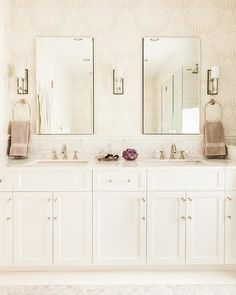 Glamorous white and beige bathroom features walls clad in Farrow & Ball Lotus Wallpaper holding two frameless medicine cabinets flanked by nickel sconces mounted above a white dual washstand fitted white shaker cabinets donning nickel and glass pulls and a white marble countertop finished with two undermount sinks and polished nickel faucets.
