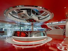 Press kit | 2222-01 - Press release | EdQuarters - M+M Creative Studio - Commercial Interior Design - Polished mirror chrome reception desk at main arrivals lobby with main stair adjacent and 2016 Corvette Sting Ray turning above - Photo credit: Benny Chan @Fotoworks