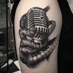 Hand Hold Microphone With Piano Keys Tattoo On Upper Sleeve