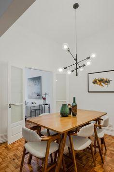 Decoração de apartamento pequeno, decoração minimal, paredes brancas, porta de madeira, sala de jantar, mesa de madeira, cadeira estofada, obra de arte.