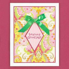 Bow-Tied Christmas Card A diamond-shape piece of patterned paper stamped with a short-and-sweet greeting and topped with a bow pops against the vibrant background of this holiday card, a piece of cardstock folded in half. Give the patterned-paper mat a solid cardstock border for a polished finish.