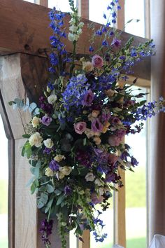 Floral hanging installation on beam containing blue Delphiniums, Stocks, spray Roses, Ocean Song Roses, Muscari, dried Lavender, created by Hannah Berry Flowers www.hannahberryflowers.co.uk for a wedding at Cain Manor