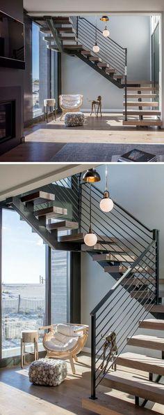 escalier design avec garde corps en métal noir et marches en bois clair, trois corps lumineux en forme de boules en verre blanc opaque, marches qui se déploient au-dessus d'un salon