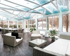 Beautiful white sunroom with a conservatory roof featuring blue glass.