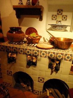 Mexican kitchen - my abuelita had something like this in her kitchen, only without the fancy tiles. Just plain bricks or whatever (brick-colored tiles?) but I remember her kitchen in Texas. It had a packed-dirt floor too. And a big 'bull's horns' mounted over the upright piano too.