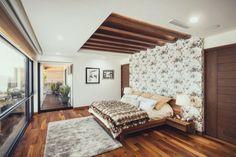 tête de lit originale en papier peint à motifs et plafond à solives