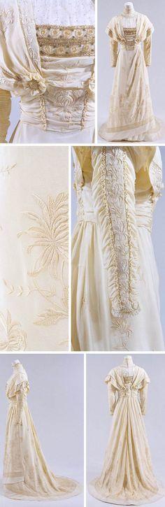 Circa 1910-1912 cream dress: silk, lace, and beads. Richly embroidered with chrysanthemums. Slightly higher waist, pintucks, and asymmetrical skirt. Via Bunka Gakuen Costume Museum.