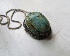Incredible 1920s Art Deco Egyptian Revival carved turquoise scarab on an ornate sterling silver setting. It can be worn as either a pendant or brooch. This piece has amazing details. It is carved with hieroglyphics on the underside.