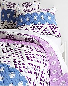 Imaginative and artsy, our hand-quilted Zhora bedding makes a bold statement. Pieced from pretty patterns and painterly stripes that range from lovely lavenders to vivid violets.100 cotton, including the midweight fillQuilt is pieced with wide horizontal bands of purple printsThree bands of prints are pieced together to form the front of the coordinating shamQuilt and sham are hand-quilted with pale orchid threadSham has clean edges, a quilted front, and a striped back, with tie…