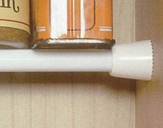 Small spice containers use shelf space in - efficiently and are difficult to find when surrounded by taller bottles and items. Use a small spring-tension curtain rod ($3) as a simple shelf. It's easy to install and strong enough to support the spices