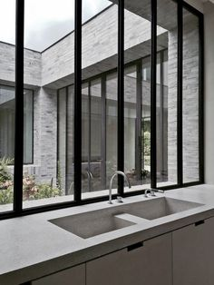 Kitchen with dark window frames. Design by Marc Merkx.