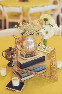 """Very pretty vignette with """"found"""" items: old books, empty frame, strand of pearls, silver coffeepot and flowers."""