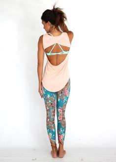 Tanned ponytailed chocolette in sleeveless split blush top revealing strappy minty sports bra, aqua/coral/brown paisley fractal yoga pants