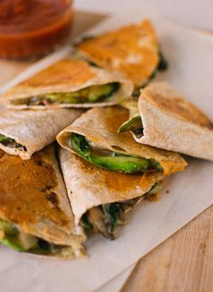 CRISPY MUSHROOM, SPINACH & AVOCADO QUESADILLAS: 1 T olive oil, 1/2 red onion, chopped; salt, 8 - 10 oz baby bella mushrooms, thinly sliced; 6 oz baby spinach, roughly chopped; 1/2 small lime, juiced; 2 1/2 cups shredded raw Jack or cheddar cheese, divided; 2 Avocados thin slices, 4 medium whole wheat tortillas, jarred red salsa.