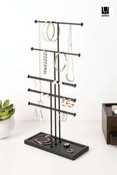 $22 · With the Trigem Jewelry Stand, five plated bars provide plenty of hanging space for all your favorite necklaces; keeping them safe, organized and tangle-free. With five tiers, Trigem is ideal for any type of necklace. The base of Trigem doubles as a jewelry holder for added accessory storage. Trigem's sleek design compliments any modern decor and the protective padded base ensures your counter or table top surface doesn't get damaged. Jewelry Tray, Jewelry Stand, Jewellery Storage, Necklace Holder, Jewelry Holder, Wall Organization, Jewelry Organization, Everything Stays, Work Stations