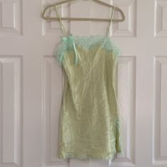 """Victoria's Secret Lace trimmed nighty Nighty is a pretty chartreuse trimmed with the pale bluish green lace and bow. He's 100% polyester and the straps are adjustable.  It has similar colored lace around the bottom and an 8"""" slit  on the left side.  It is been gently washed and worn and has no rips no stains.  Picture three is the closest to the true color. Victoria's Secret Intimates & Sleepwear"""