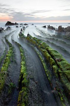 Tilted interbedded sedimentary flysch along a coastline.