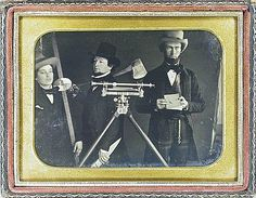 Occupation. Surveying crew. Three men with surveying instruments and tools. One man holds the rod; another holds the axe and wooden stake; another runs the book. In foreground is the surveying instrument on a tripod.