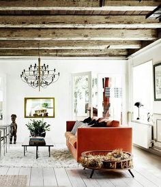 The living room features wooden beams and a bold orange sofa, fur pieces add coziness and texture - Scandinavian Home With Rustic Elements And Ocean Views Scandi Home, Scandinavian Home, Oranges Sofa, Living Room Designs, Living Spaces, Home Interior, Interior Design, Wooden House Design, Gravity Home