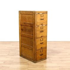 This rustic file cabinet is featured in a solid wood with a distressed oak finish. This tall filing cabinet has 4 spacious file drawers, a missing side panel and brass hardware. Perfect for a home office workstation! #americantraditional #storage #filecabinet #sandiegovintage #vintagefurniture