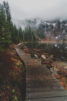 photo:  wood pathway winds around mountain lake ... fog entering over snow dusted peaks ....