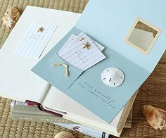 Greeting Card and Bookplates Inside  Hot-glue a miniature sand dollar and a raffia-trimmed pocket inside. For the bookplates, run adhesive labels with a preprinted striped design through a color printer. Decorate each with a miniature starfish.