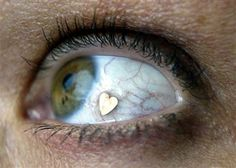 "A new Dutch fashion trend.  Cosmetic surgery.  It's called ""eyeball"" jewelry. That heart is actually  a piece of jewelry inserted into the membrane of the eye."