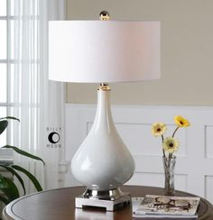 "This lovely table lamp features a ceramic base with an ivory finish and a polished nickel plated bottom. The lamp is topped off with a round hardback shade made with ivory linen fabric. It measures 17"" in diameter (with shade) X 30""H and takes a single 100 watt max bulb. Click on images for greater detail."