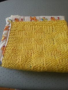 Lovely handknittet baby blanket with colourful backing. On sale on Ebay: