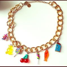 Dylan's Candy Bar exclusive collaboration necklace Gold-colored chain link necklace with adjustable hook clasp in the back. Includes charms designed by Dylan Lauren, daughter of the renowned Ralph Lauren and owner of Dylan's Candy Bar (a popular candy shop in New York). Charms include chocolate bar, gummy fish, two rainbow lollipop suckers, gummy bear, cherries, and a small gimbal machine. Feel free to ask any questions! Really fun accessory for parties and all you candy-lovers out there…