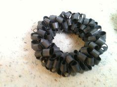 Armband gemaakt van fietsband. Knip smalle reepjes van een fietsband. Draai de reepjes binnenstebuiten. Bij de 'knikken' prik je met naald en elastiek in het midden er door heen. Je rijgt zoveel reepjes als je armband nodig heeft.